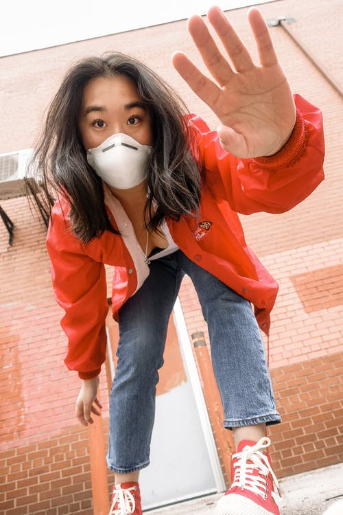 Low angle of trendy Asian female in respiratory mask saying hi while leaning forward near building with brick wall and looking at camera during quarantine period in town