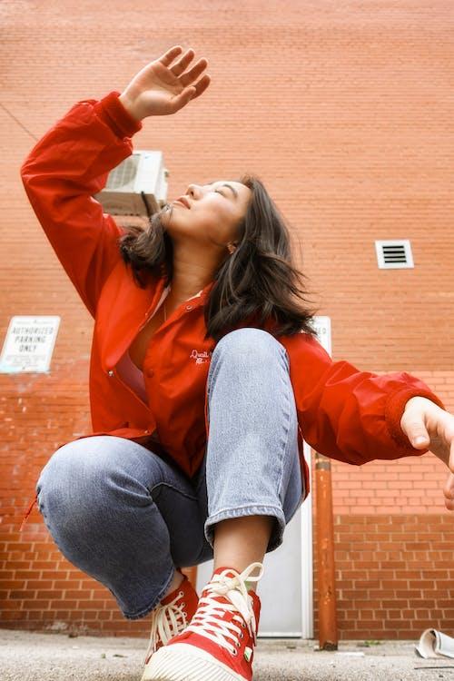 Stylish ethnic woman raising arm with closed eyes while squatting