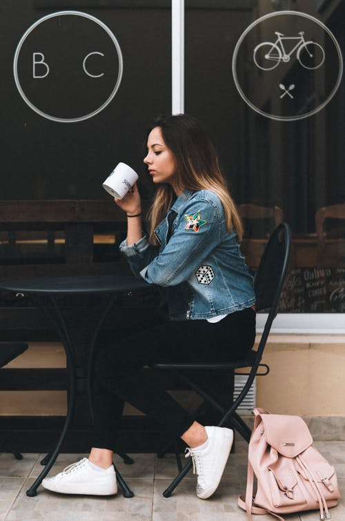 Woman in Blue Denim Jacket Holding White Ceramic Mug Sitting on Black Chair