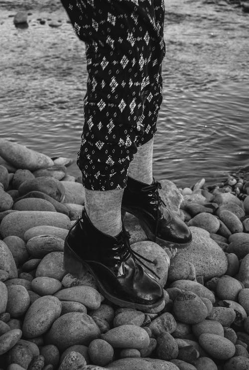 From above side view black and white of crop unrecognizable trendy female in trousers with ornament and leather footwear standing on stones near pond with rippled water