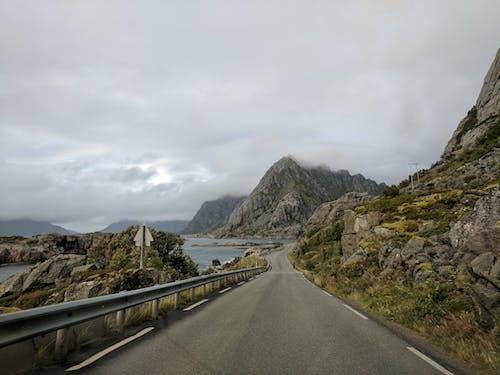 Gray Concrete Road Near Mountain Under White Sky