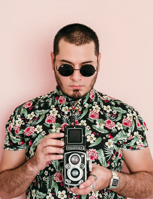 Man in Black Sunglasses Holding Black and Silver Camera