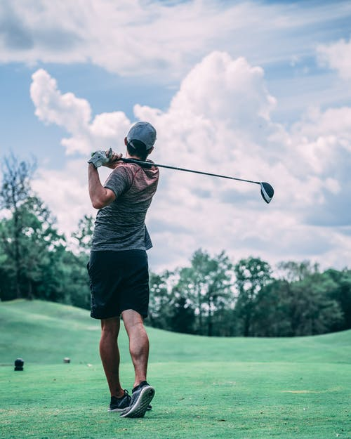 Unrecognizable golfer with golf club playing in field under sky