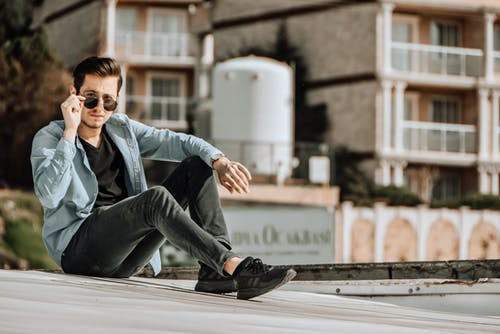 Stylish masculine man in sunglasses sitting on building roof