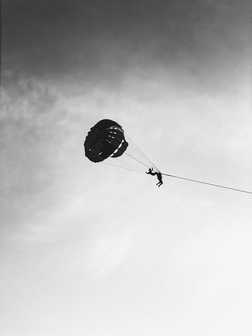 Grayscale Photo of Person Riding Parachute