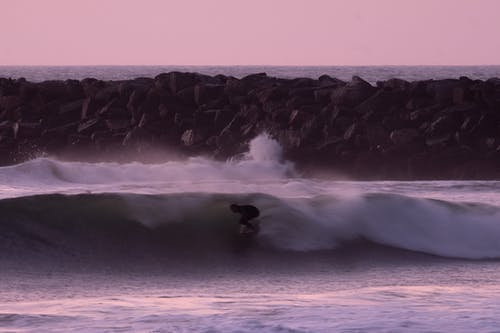 Athlete practicing surfing on wavy sea at bright sunset