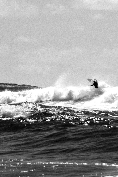 Grayscale Photo of Man Surfing on Sea Waves