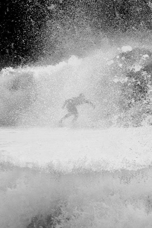 Black and white silhouette of faceless sportsman practicing surfing on foamy sea with splashing water in stormy weather