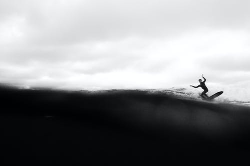 Grayscale Photo of Person On Surfboard