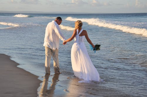 Man and Woman in Wedding Dress Walking on Beach