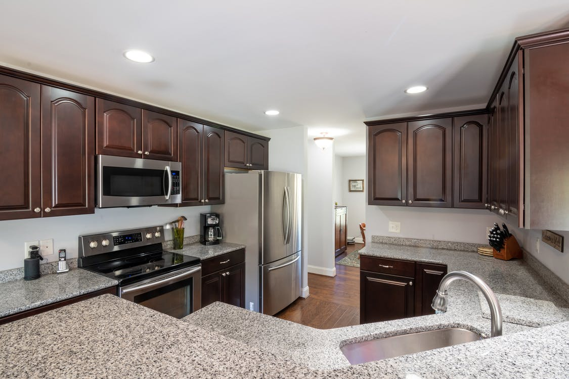 Wooden Kitchen Cabinets And Marble Top Counters In Kitchen