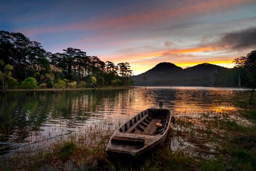Old boat near lake and mountains under sky at sunset