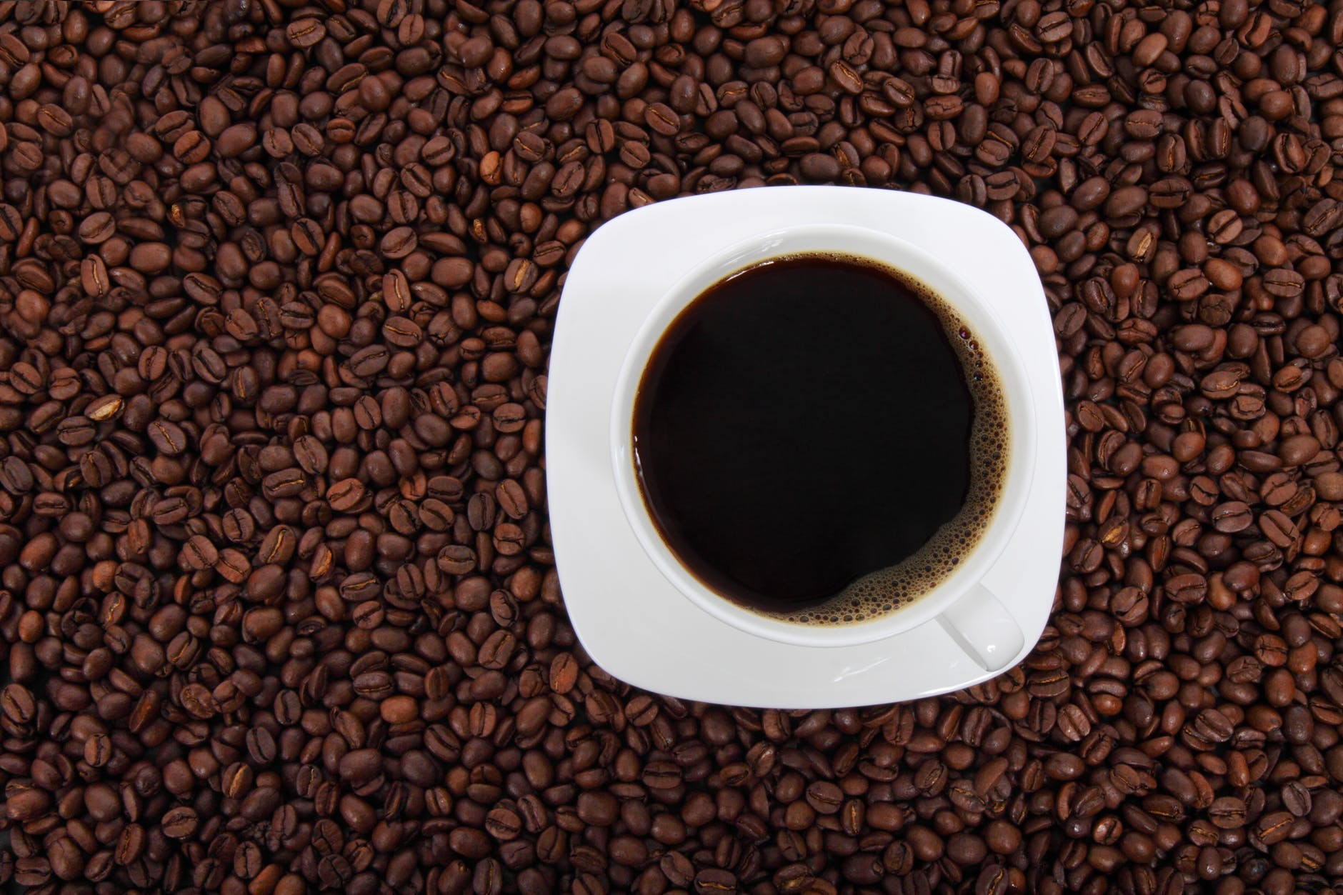 cup of coffee surrounded with coffee beans