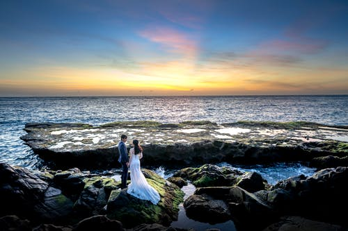 Photo of Couple Standing on Rocky Seashore