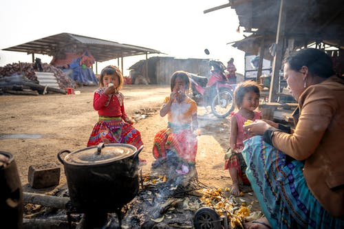 Photo of Woman Cooking While Sitting Near Her Children