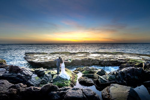 Photo of Couple Posing on Rocky Seashore During Golden Hour