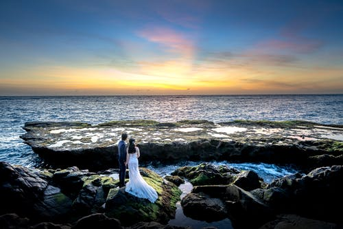 Photo of Couple Standing on Rocky Shore During Golden Hour