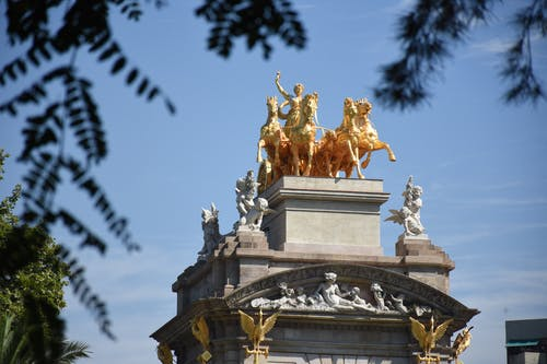 From below of top of Golden fountain located near green trees under blue sky with clouds in sunny day