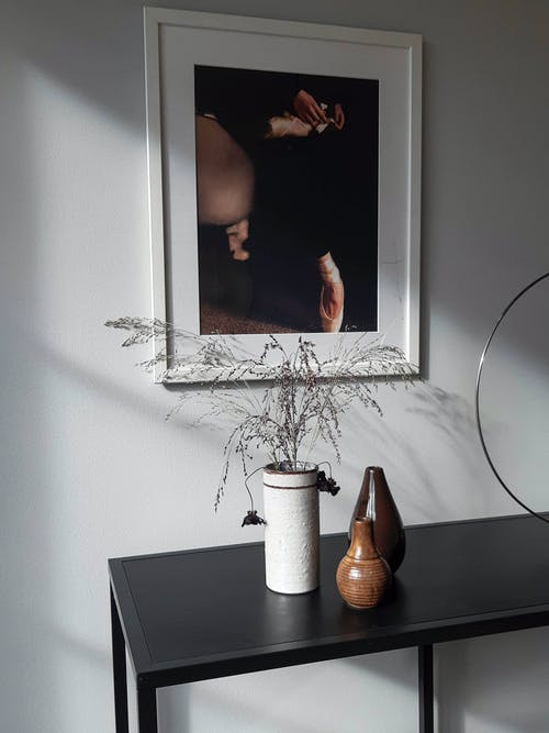 Table with vases placed near wall with picture