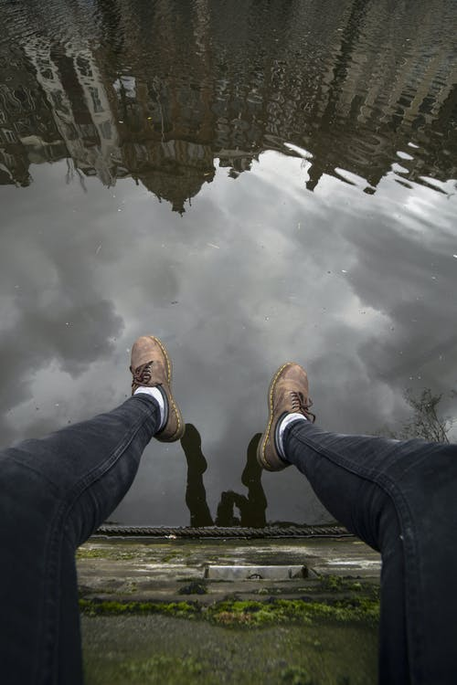 From above crop anonymous male in casual clothes resting on mossy stone canal front edge and hanging legs down over muddy water with reflection of sky and buildings