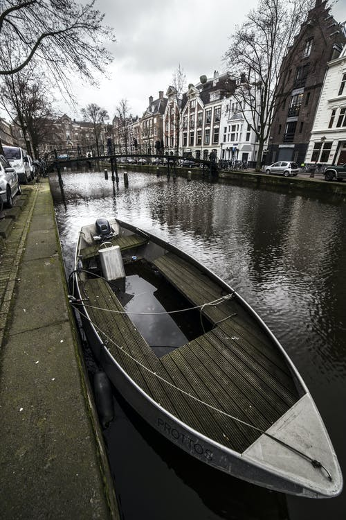Modern boat moored on canal against cozy houses of Amsterdam