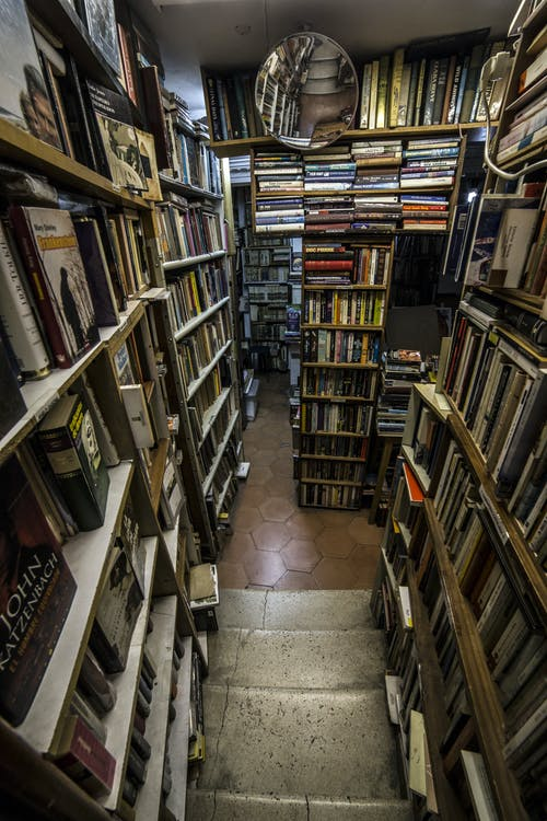 Old fashioned bookstore with aged shelves loaded with assorted various books and magazines