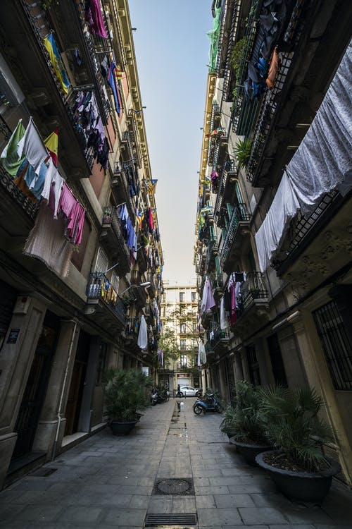 From below of narrow passage between residential buildings with plenty of linens drying on balconies on clear day