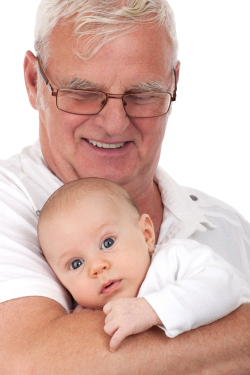 Man in Black Frame Eyeglasses Carrying a Baby