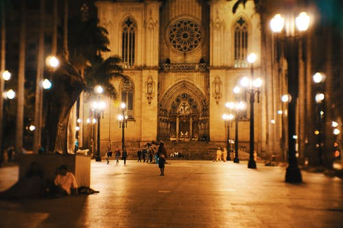 Facade of ancient Catholic church located on square with lanterns and palm trees at night