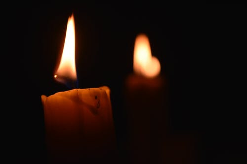 Candles with burning flame in darkness