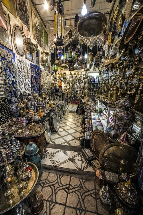 Interior of traditional oriental market stall with various authentic lamps and souvenirs hanging on walls or heaped on stands