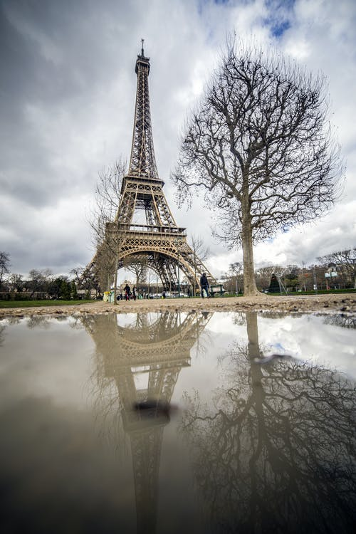 Eiffel tower in spring trees against cloudy sky