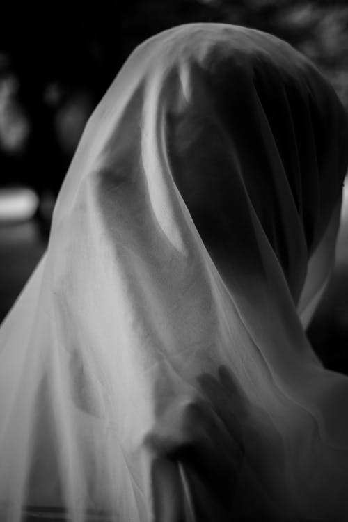 Black and white of unrecognizable person covering face with translucent cloth against blurred background