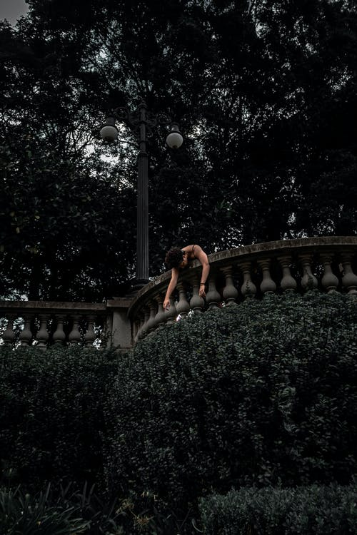 Young woman bending over stone balcony railing in park