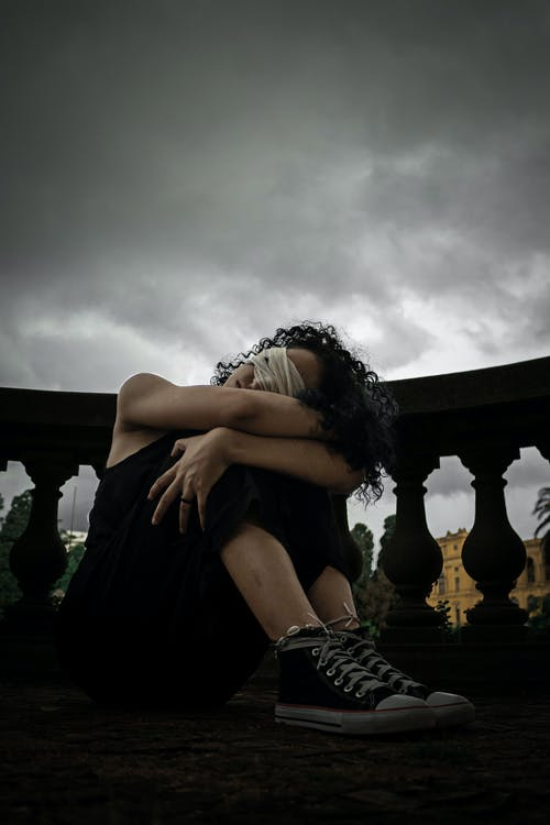 Full body of anonymous depressed lady with curly hair and sitting on balcony hugging knees with covered eyes on overcast day
