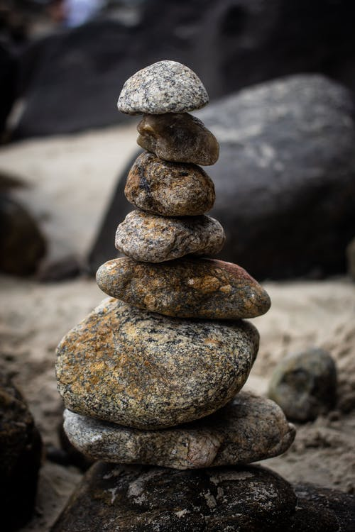 Mini tower made of various stones on rocky beach