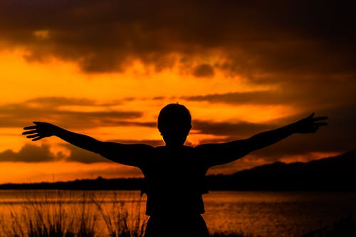 Unrecognizable woman with raised arms admiring sunset over sea