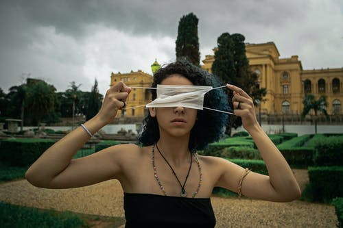 Serious young ethnic female with curly hair in light top covering eyes with medical mask while standing in city park against cloudy sky