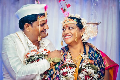 Cheerful Indian couple smiling during wedding celebration