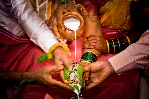 Crop newlywed Indian couple during traditional wedding ritual