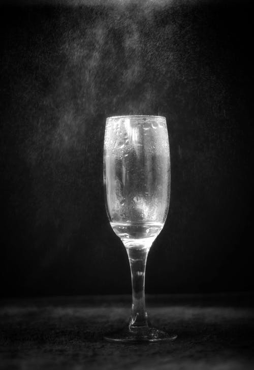 Black and white of glass for champagne with remains of alcohol drink placed on table