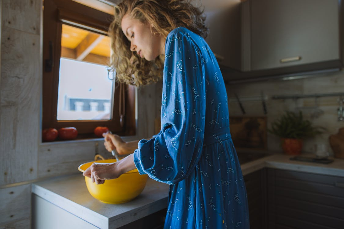 Woman in Blue Long Sleeve Dress Holding Yellow Bowl