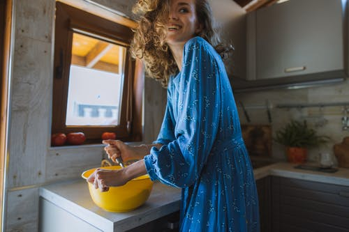 Woman in Blue Long Sleeve Dress Holding Yellow Plastic Bowl