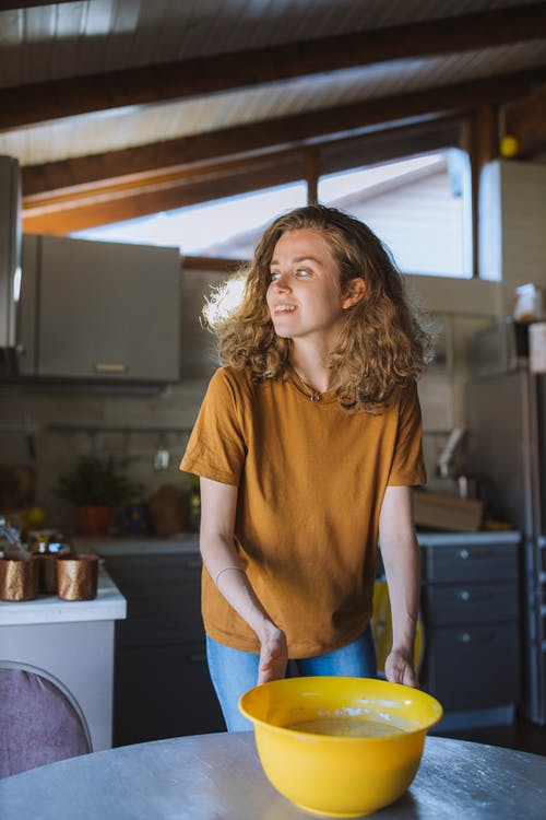 Woman With Yellow Bowl in the Kitchen
