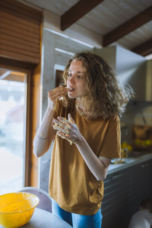 Woman Tasting Dough From Her Hands