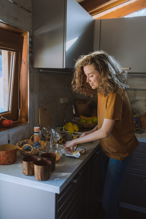 Woman in Brown Shirt Cutting Butter