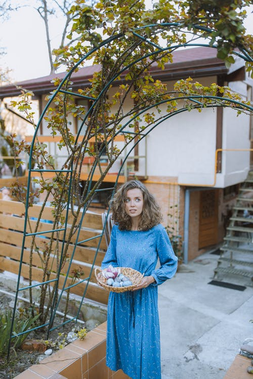Woman in Blue Long Sleeve Dress With Eggs Basket