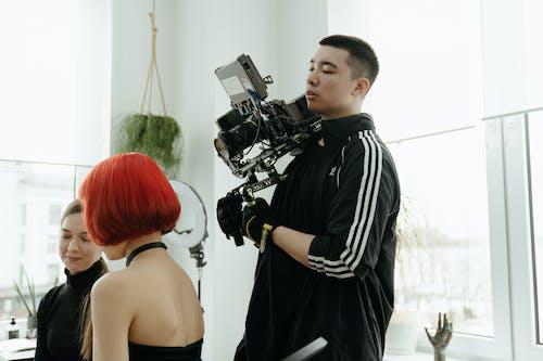 Man in Black and White Stripe Polo Shirt Holding Black Dslr Camera
