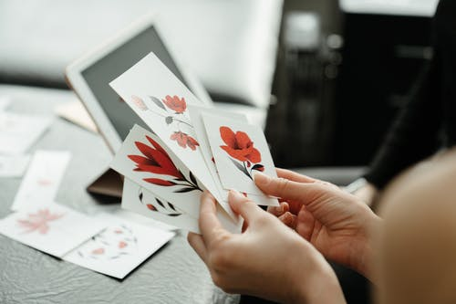 Person Holding White and Red Flower Card