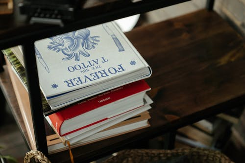 White and Blue Book on Brown Wooden Table